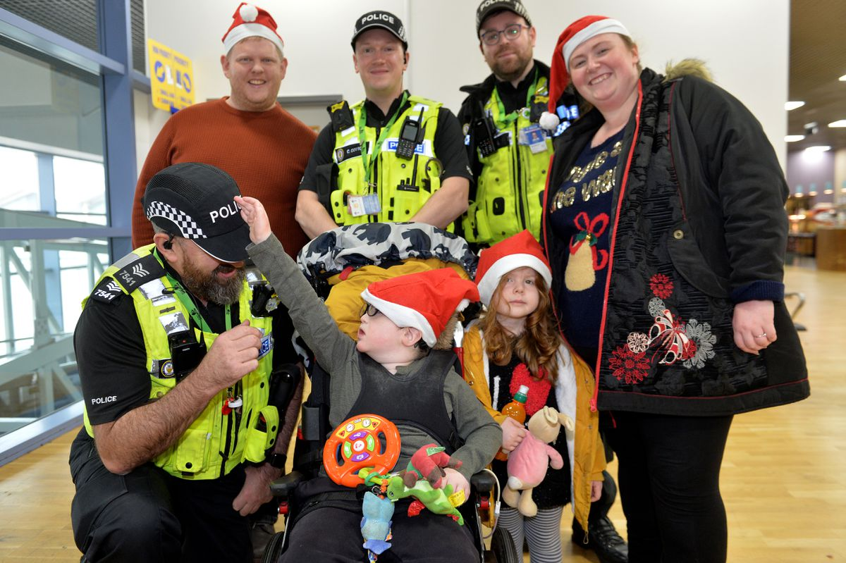 Jonathan Waring and partner Rachel O'Donnell with their children Charlie and Isobel, from Walsall, meet the airport police
