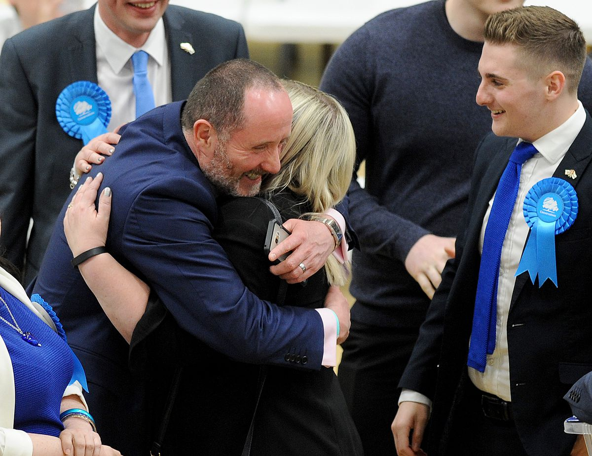 Walsall North MP Eddie Hughes hugs Louise Harrison, who held onto her Bloxwich West seat