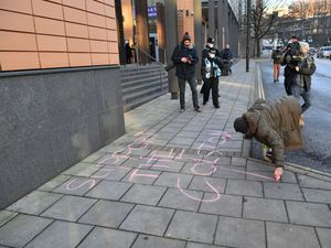 A woman writes Support The Colston 4 in chalk outside Bristol Magistrates' Court (Ben Birchall/PA)