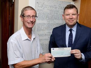 Keith Harrison, editor of the Express & Star, presenting the winner of the local history symposium David Taylor with his prize, standing in front of a copy of the first edition of the Express & Star