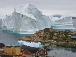 Greenland village watches looming iceberg