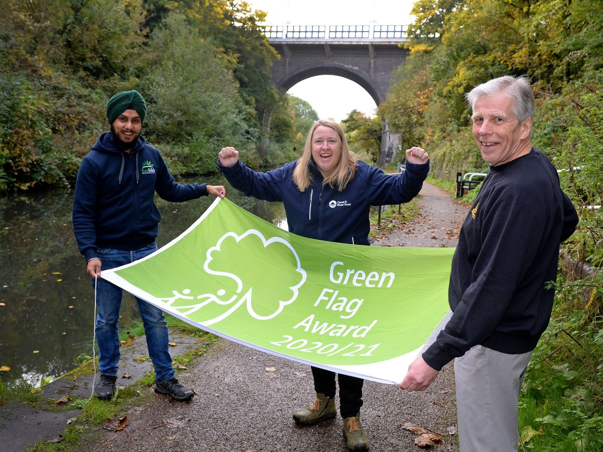 Prubhjyot Singh, Audrey O'Connor, and Bob Fox celebrate the Green Flag award for the Main Line Canal
