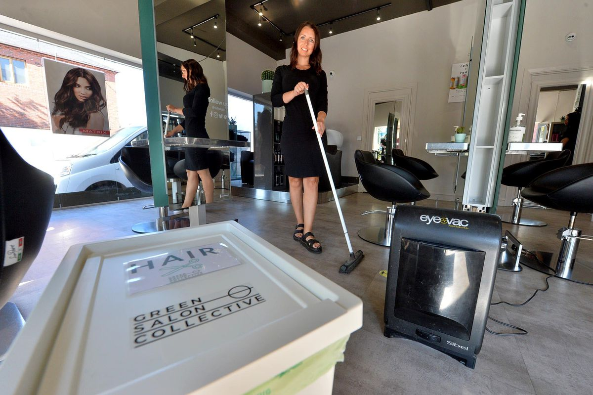 Owner Amy Church with a vaccum for picking up hair and the recycling box that they put it in for collection