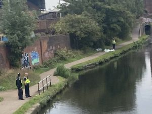 Police at the scene next to the canal where the woman was found. Photo: Barry Dunn