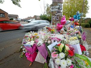 Tributes fill the spot where four people died after a car crash in Bromley Lane, Kingswinford
