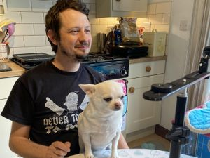 Paul Spicer with his Chihuahua Mojo Jojo, taking part in an online forum from his kitchen in Brewood, Staffordshire