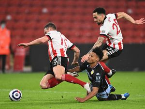 """Aston Villa's Ollie Watkins (floor) battles for the ball with Sheffield United's Kean Bryan (right) and Phil Jagielka during the Premier League match at Bramall Lane, Sheffield. Picture date: Wednesday March 3, 2021. PA Photo. See PA story SOCCER Sheff Utd. Photo credit should read: Stu Forster/PA Wire...RESTRICTIONS: EDITORIAL USE ONLY No use with unauthorised audio, video, data, fixture lists, club/league logos or """"live"""" services. Online in-match use limited to 120 images, no video emulation. No use in betting, games or single club/league/player publications.."""