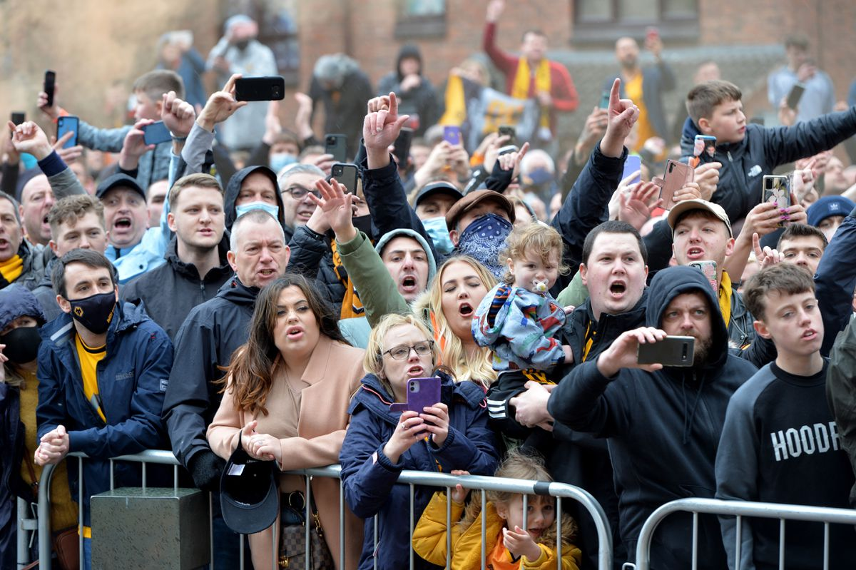 Wolves fans celebrate as the coaches turn up outside Molineux