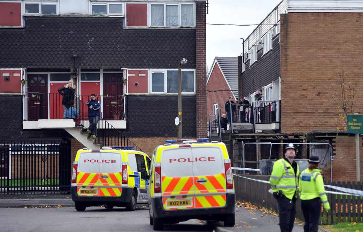 Residents outside their flats watch the operation on Wednesday