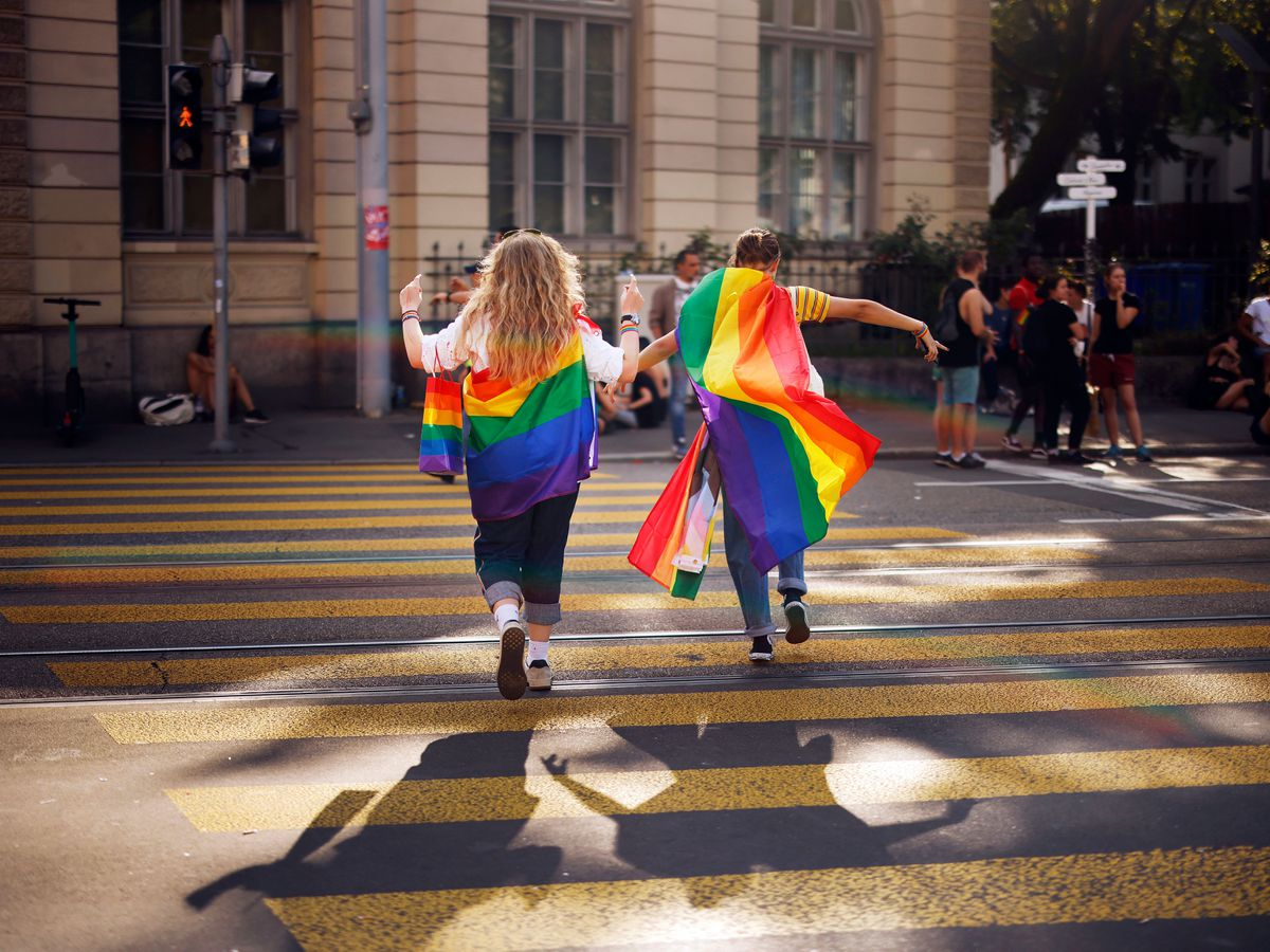 Two people cross a road draped in rainbow coloured flags