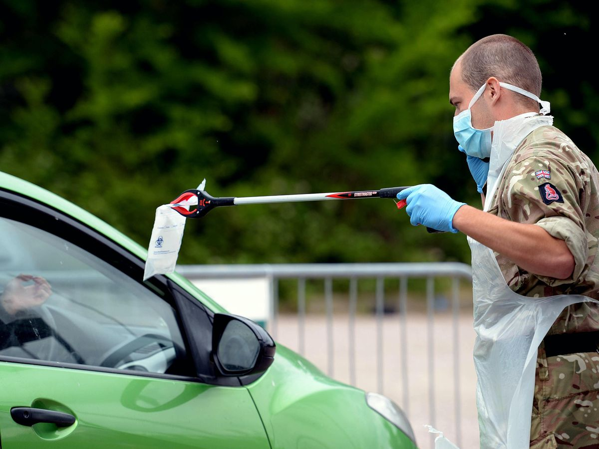 A person passes a completed coronavirus self-test package through a car window