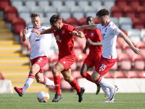 Kiddersminster Harriers' Ethan Freemantle battles against Wrexham's defenders during the Pre-Season friendly match at Aggbrough, Kiddersminster.