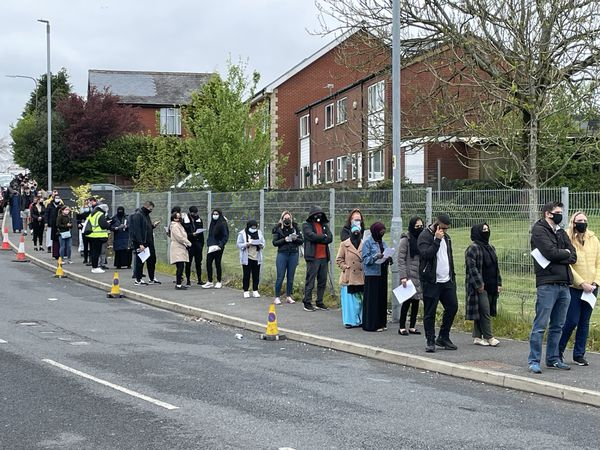 People queue for the vaccination centre at the Essa Academy in Bolton
