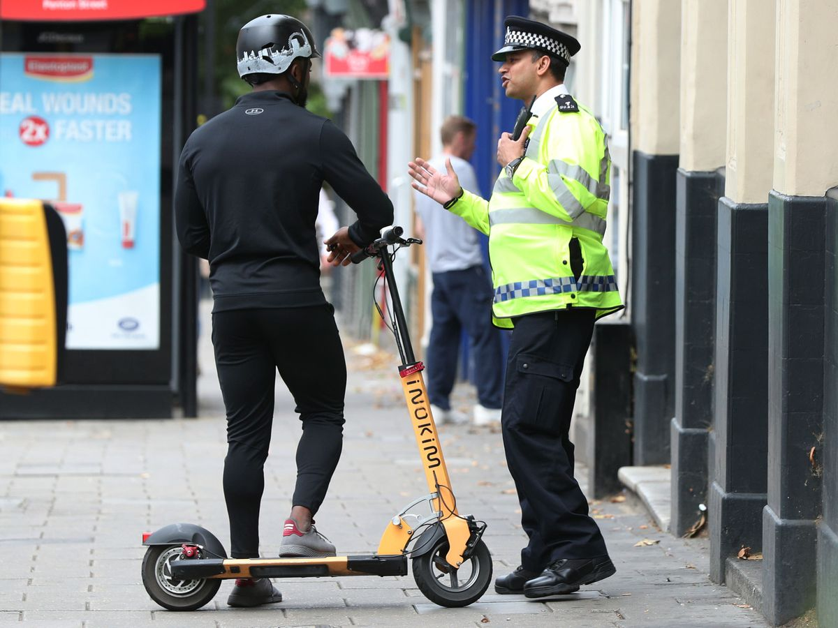 An e-scooter rider is spoken to by a police officer