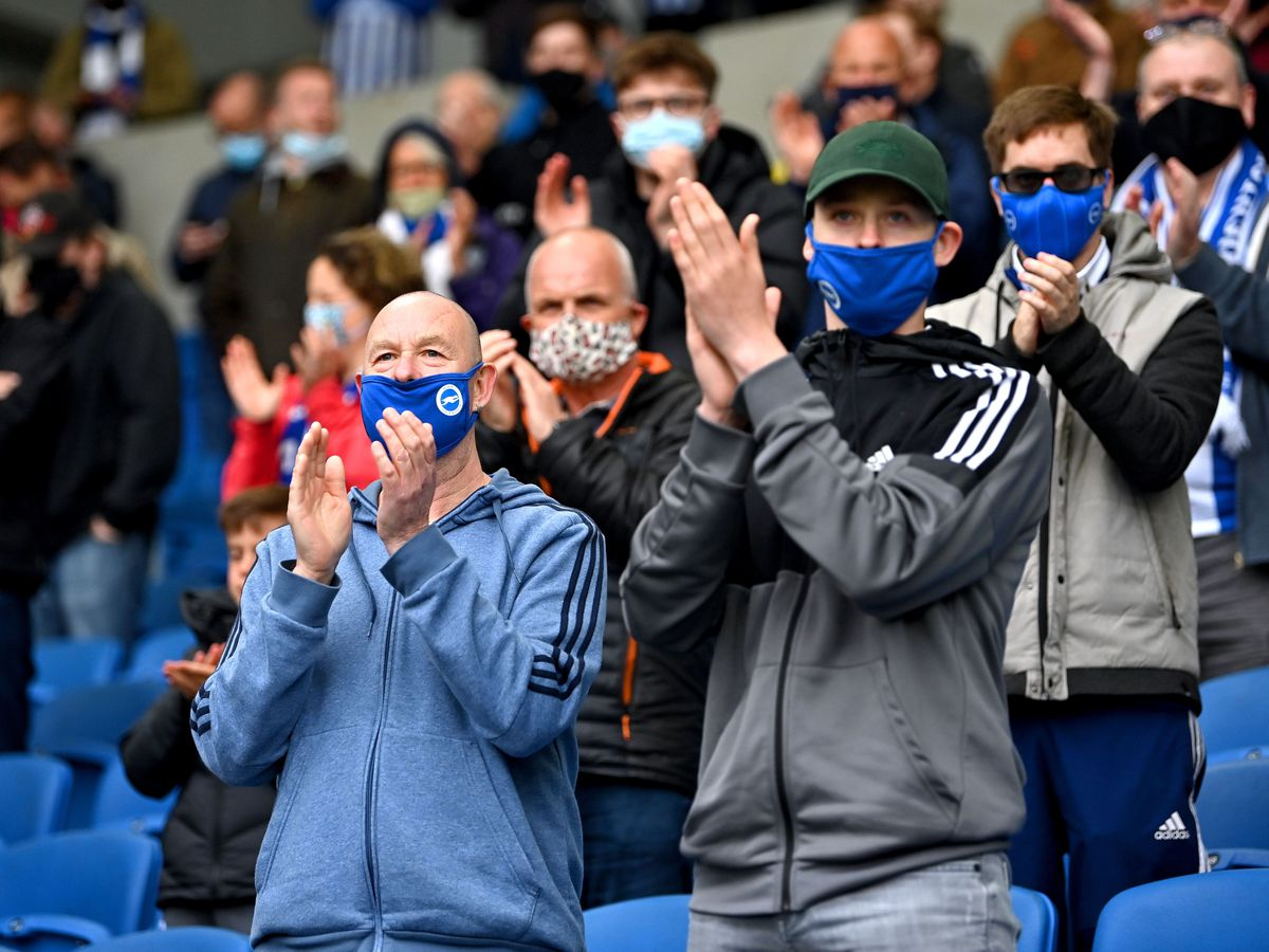 Fans in masks applaud their team