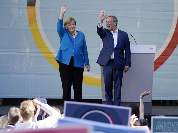 Chancellor Angela Merkel and Governor Armin Laschet wave to supporters at an election campaign event