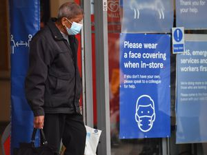 A shopper wearing a face mask leaves Tesco