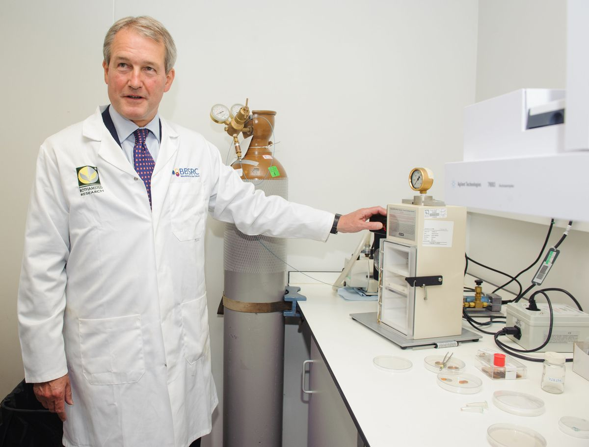 Owen Paterson tries a particle gun used in the testing of genetically modified crops during a visit to Rothamsted Research, in Harpenden, Hertfordshire