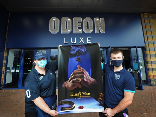 Cinema hosts Ellie Wyke and Aaron Robinson with a poster for The King's Man, which is on in 2021, at Odeon Luxe Telford