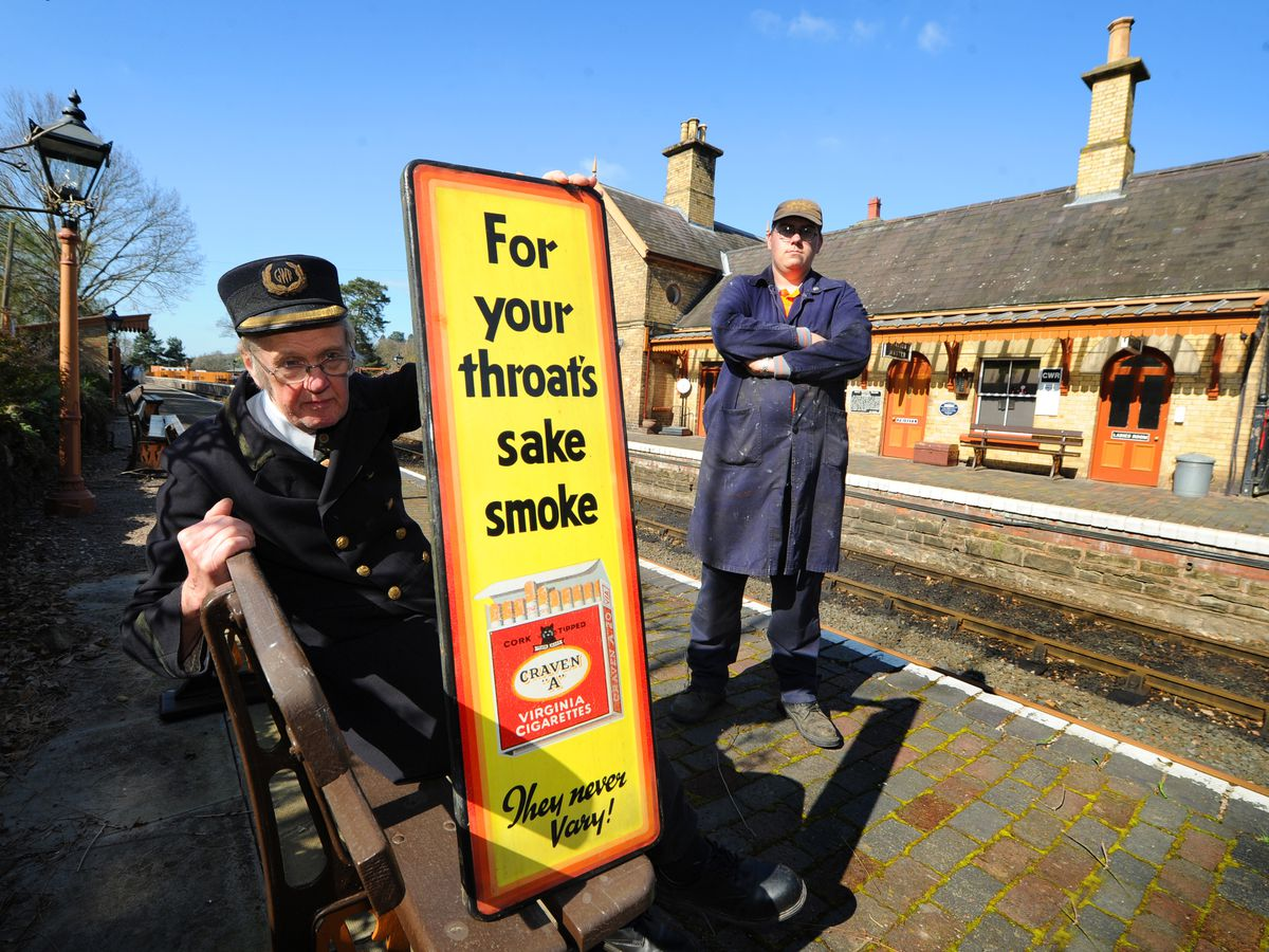 Station master Ian Latimer, with volunteer Leonard Warrington, holding one of the few remaining signs at Arley Station