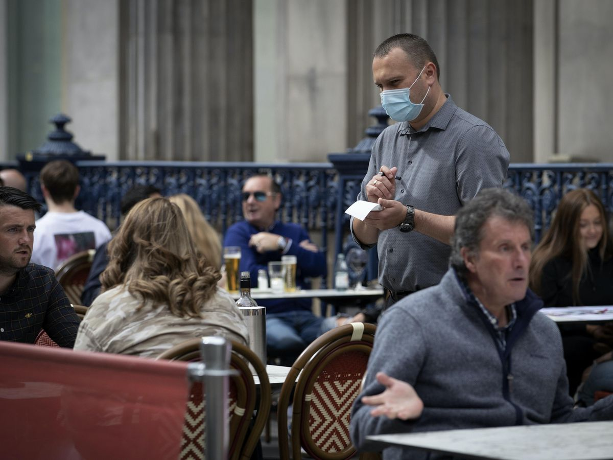 A waiter takes orders on the street at Di Maggio's outdoor restaurant area in Glasgow city centre