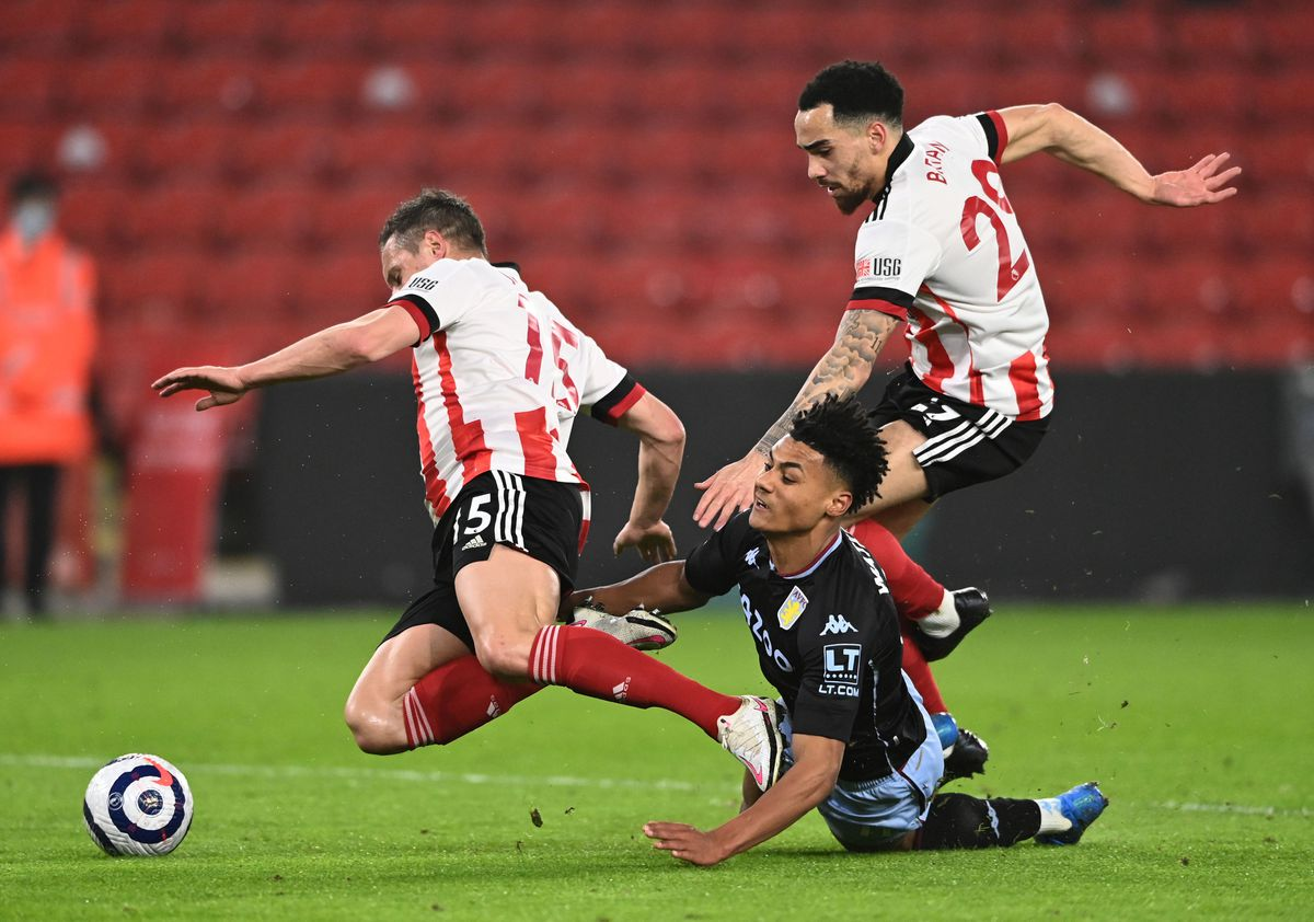 Aston Villa's Ollie Watkins (floor) battles for the ball with Sheffield United's Kean Bryan (right)