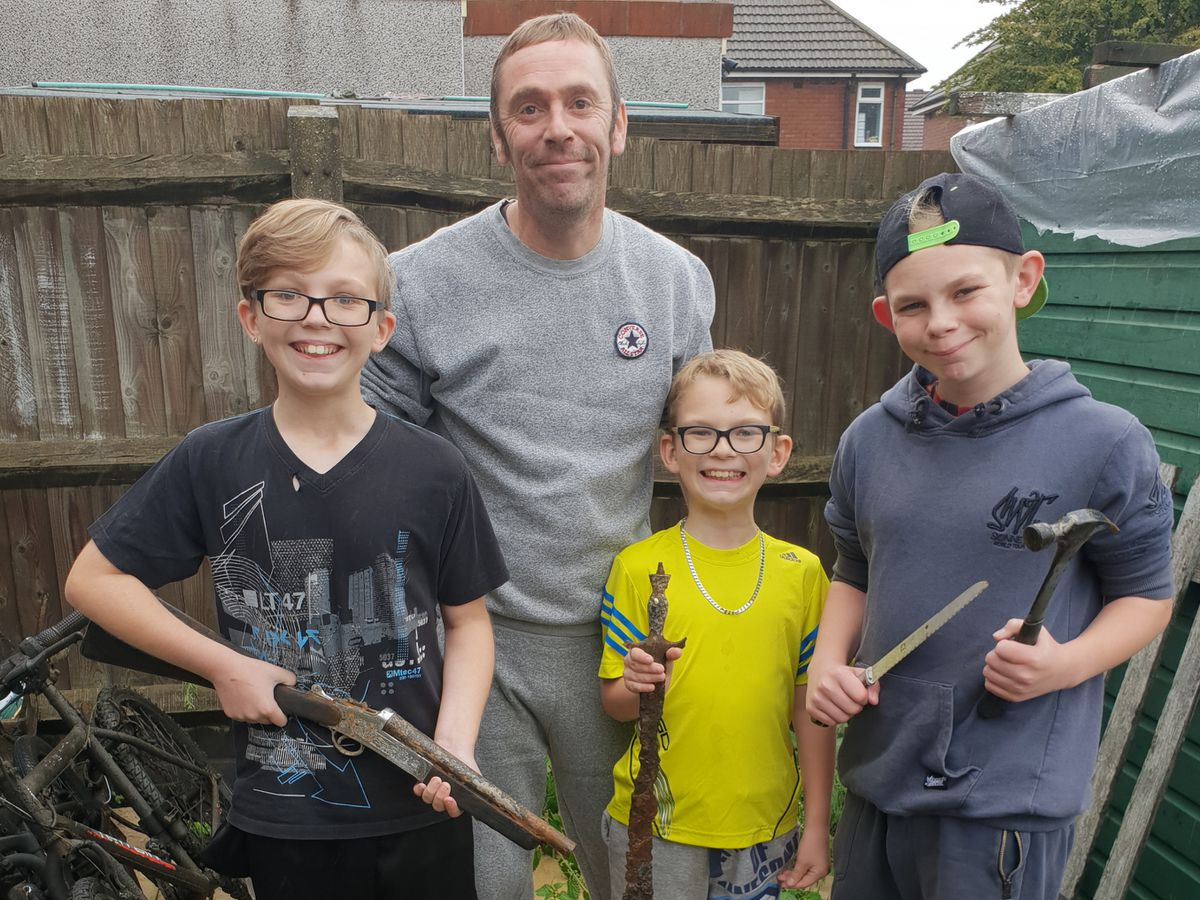 Twelve-year-old McKenzie, left, who found the shotgun, with his father Scott Hargood, 10-year-old Finley and 14-year-old Logan
