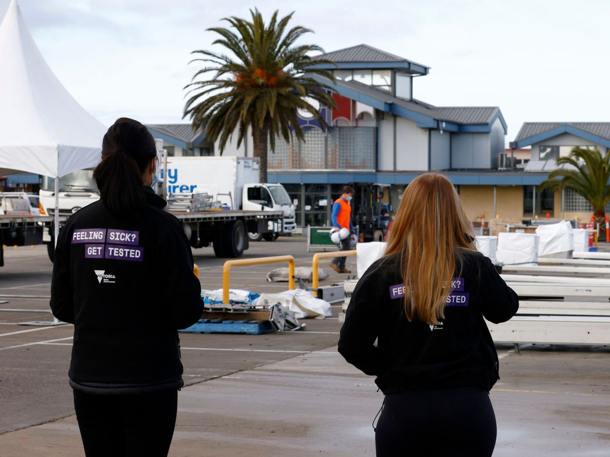 Healthcare staff watch as workers construct a pop-up Covid-19 testing site in Melbourne (Daniel Pockett/AAP