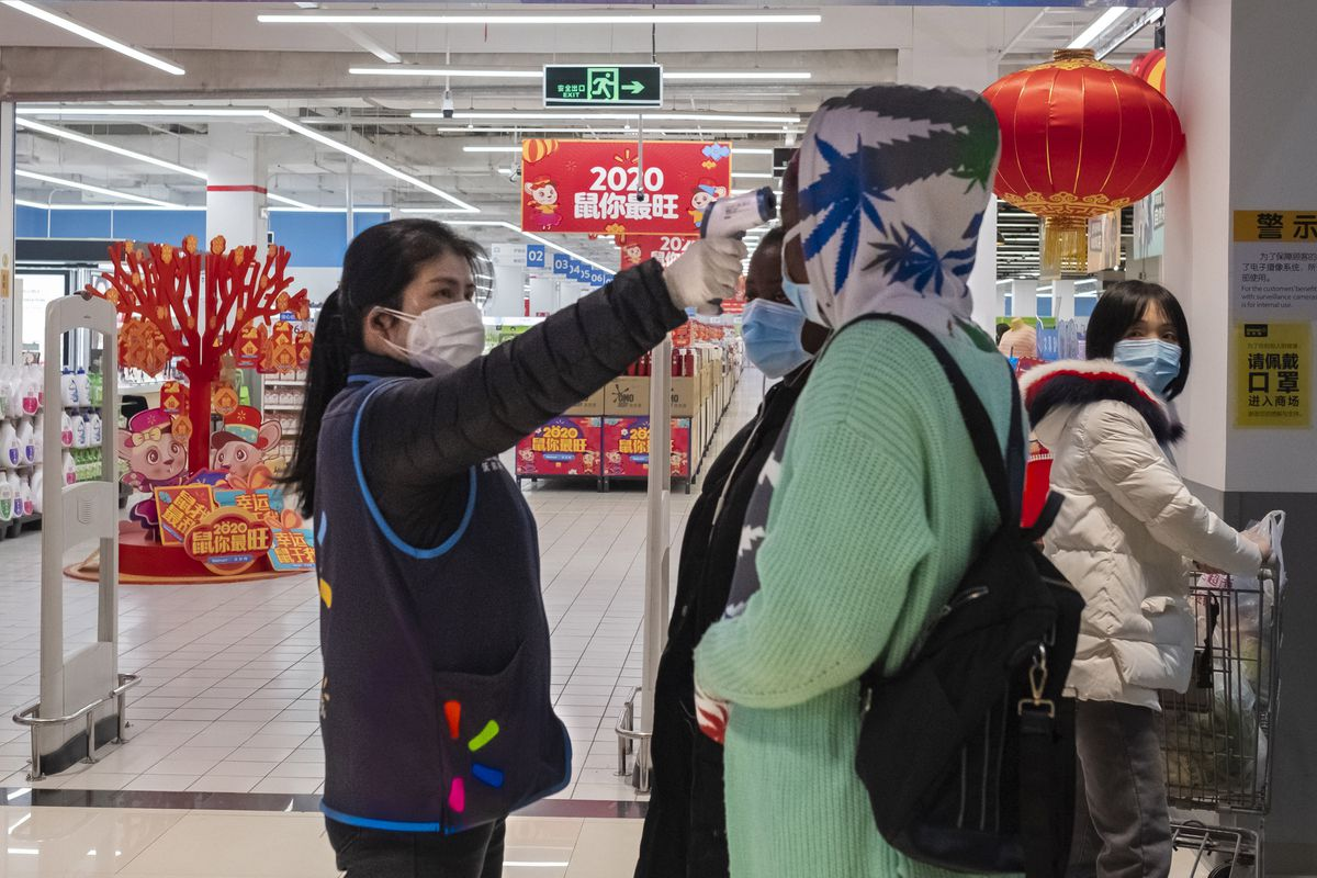 A worker takes the temperature of a customer at the entrance of a Walmart store in Wuhan in central China's Hubei Province