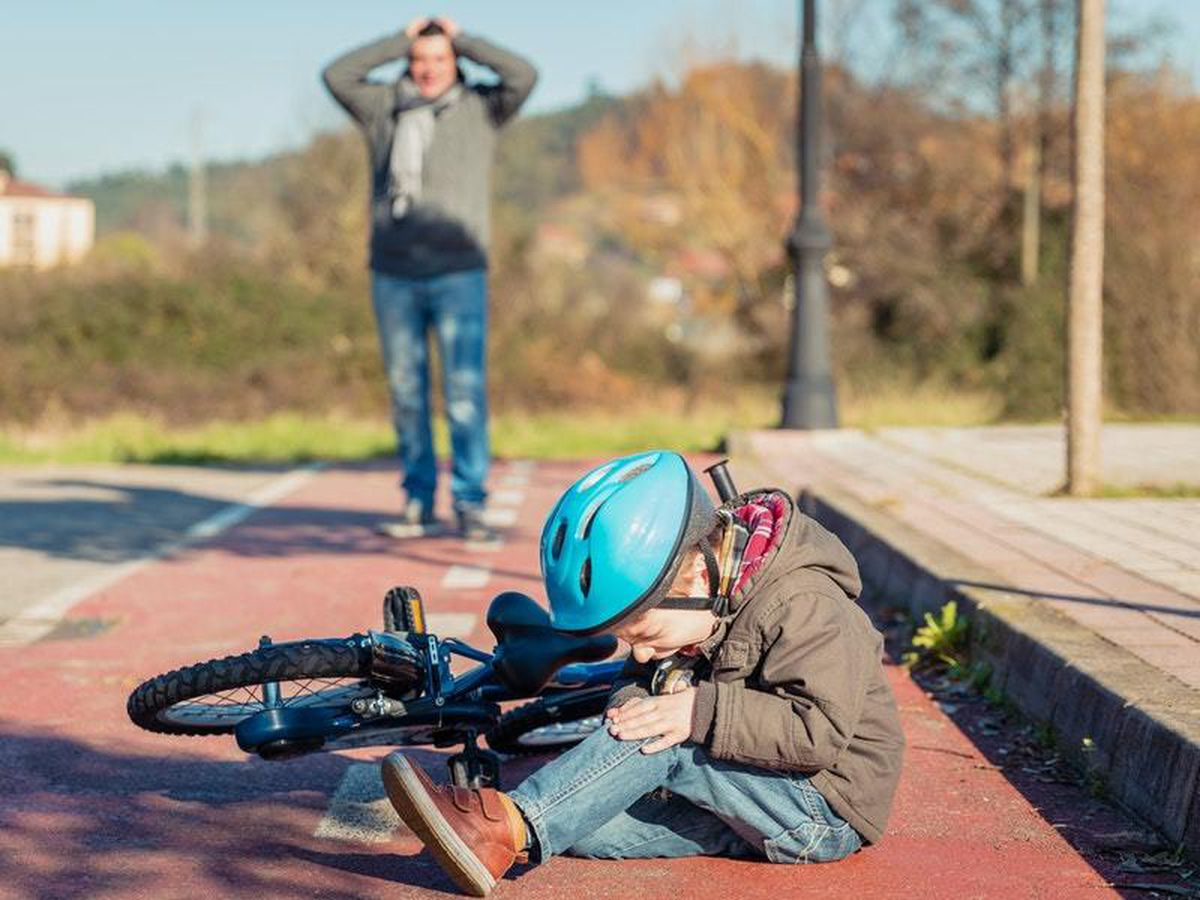 A boy cries after hurting his knee in a fall from his bike