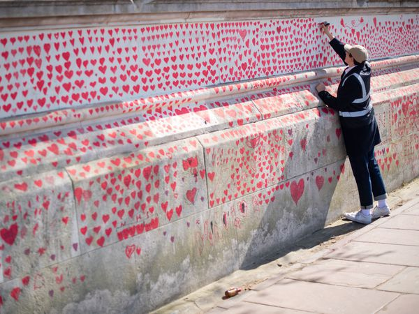 A volunteer adds hearts to the Covid memorial wall in Westminster