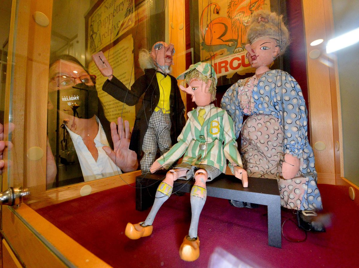 Some of the puppets on display with museum staff member Sue