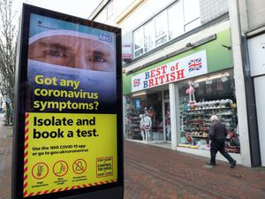 A person walks past a Government coronavirus sign on Commercial Road in Bournemouth, Dorset