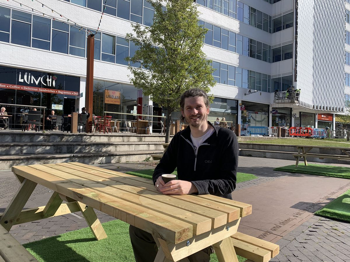 Luke Crane tries out one of the new picnic tables in Golden Square