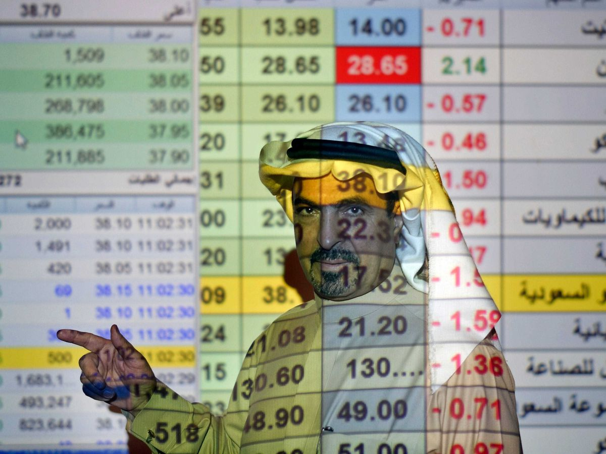 A trader in front of a screen displaying Saudi stock market values