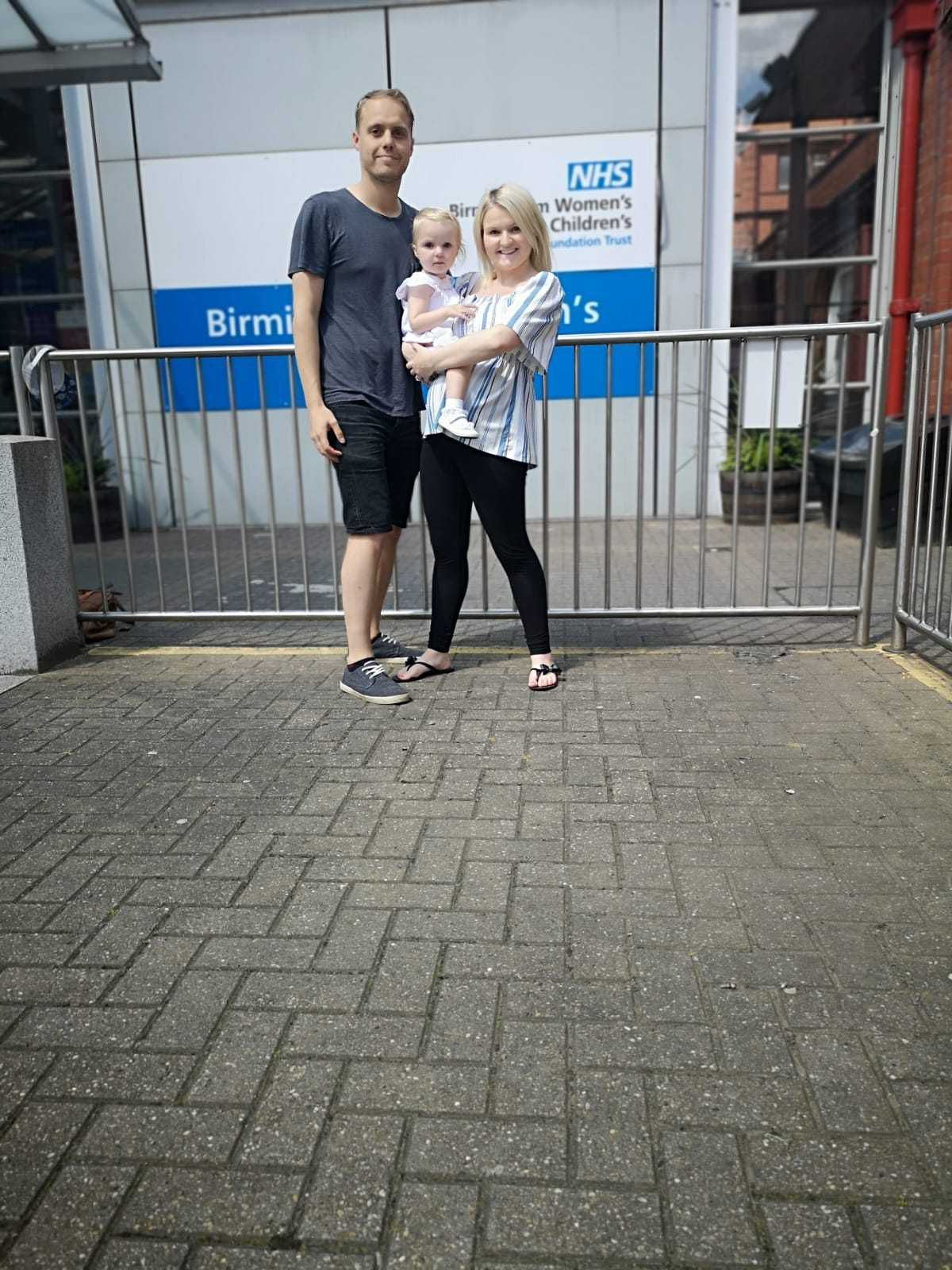 A family photo outside Birmingham Children's Hospital. Darren, Jade and Mabel
