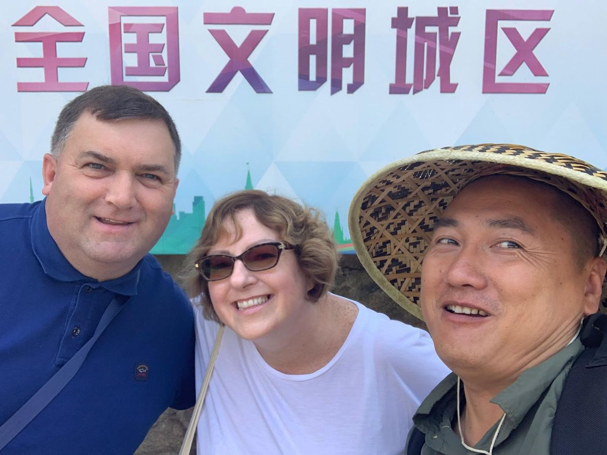 Greg and Claire Elliott with their guide at the base of the Wall of China last year.