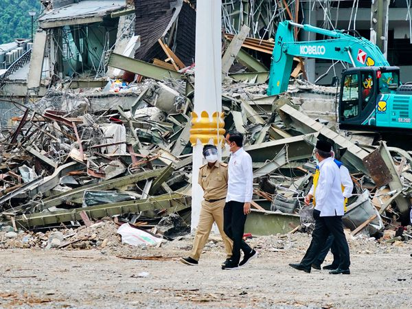 President Joko Widodo, centre, talks to an official as he inspects an earthquake-damaged government building in Mamuju, West Sulawesi