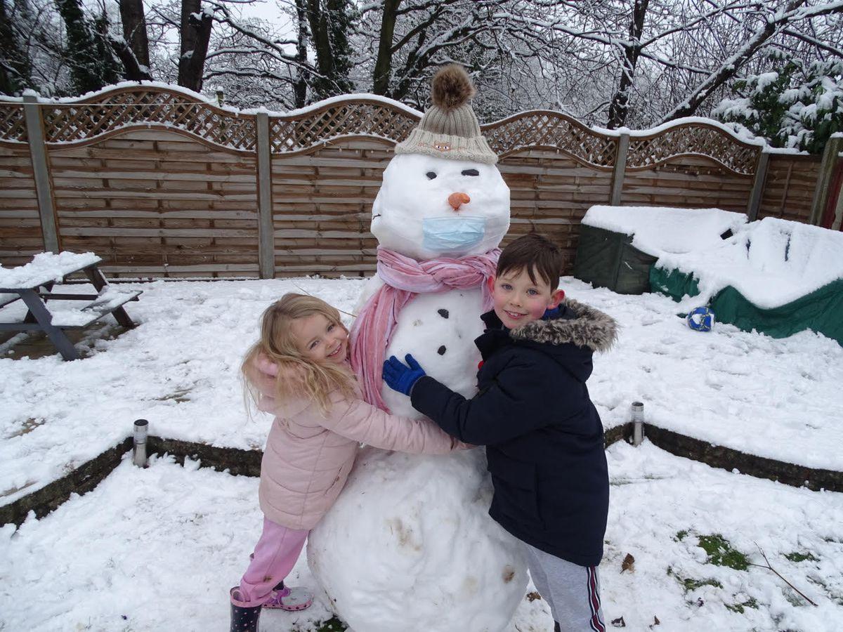 Lucy Harris and Jacob Harris with Coronovirus Snowman ibn Codsall. Pic: Laura Harris.