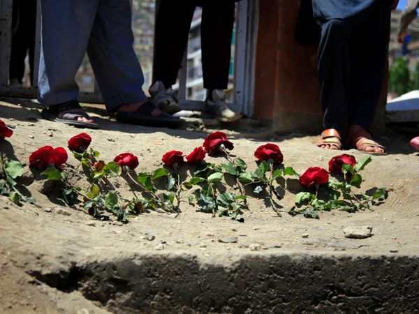 People puts flowers outside a school after a deadly attack on Saturday, in Kabul, Afghanistan