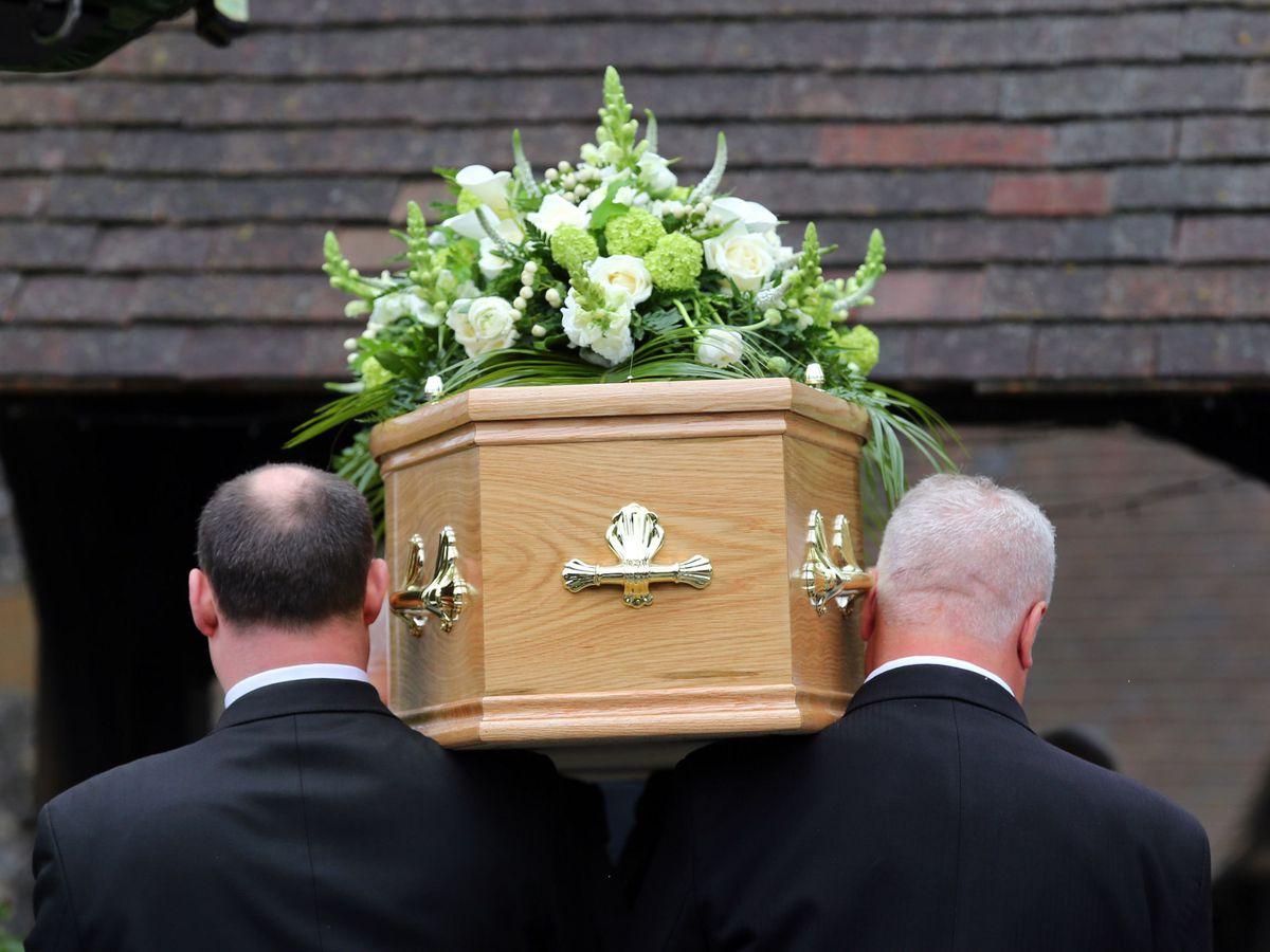 Pallbearers carry a coffin