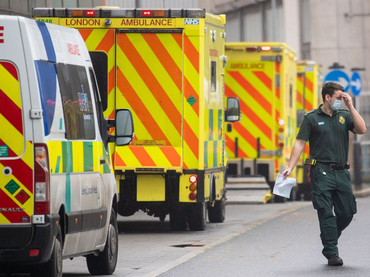 A paramedic walks past a line of ambulances outside the Royal London Hospital