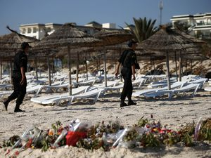 Police officers patrol the beach in Sousse after the 2015 terror attack