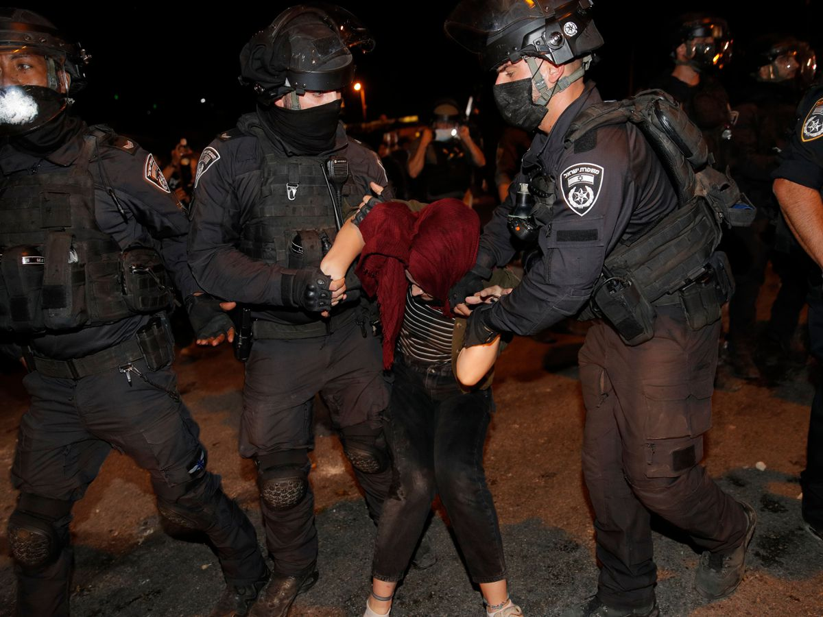 Israeli police officers detain a Palestinian demonstrator during a protest against the planned evictions of Palestinian families in the Sheikh Jarrah neighbourhood of east Jerusalem
