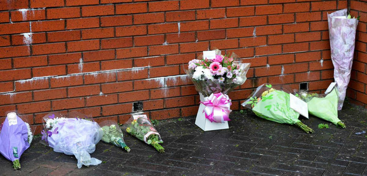 The first flowers left in tribute outside the house