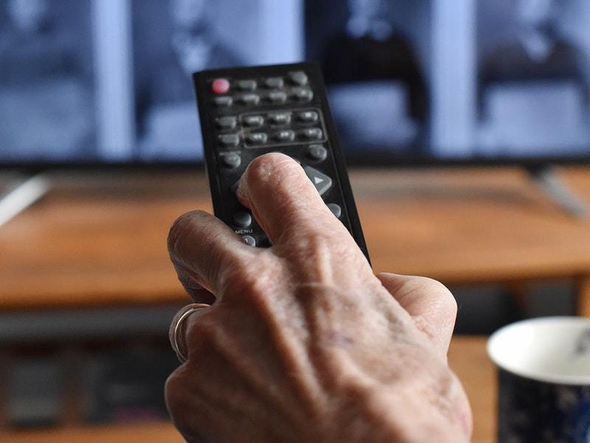 Someone pointing a remote at a TV