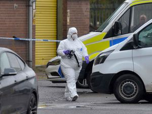 A forensic officer at the scene where a man was shot dead
