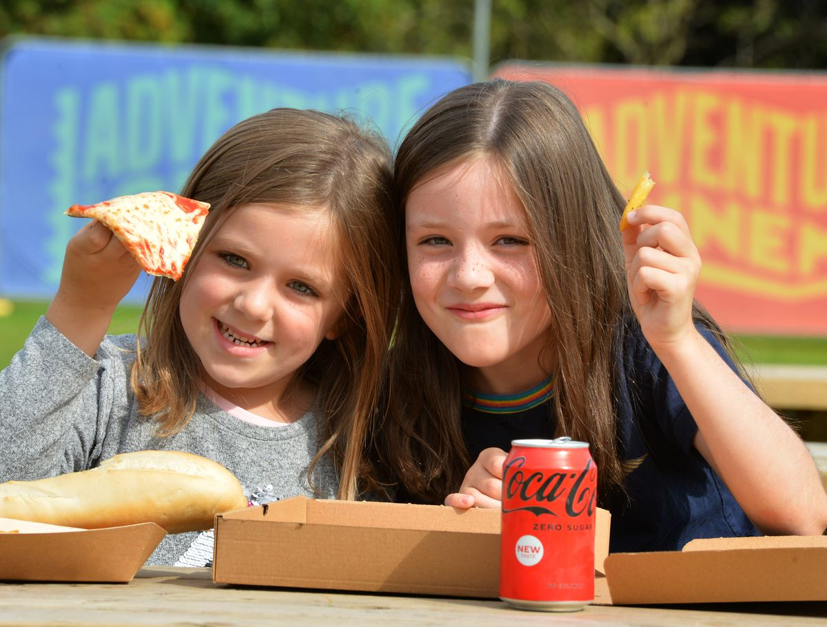 Hannah Burke, five, and Jessica Burke, eight enjoy a pizza and fries at the festival