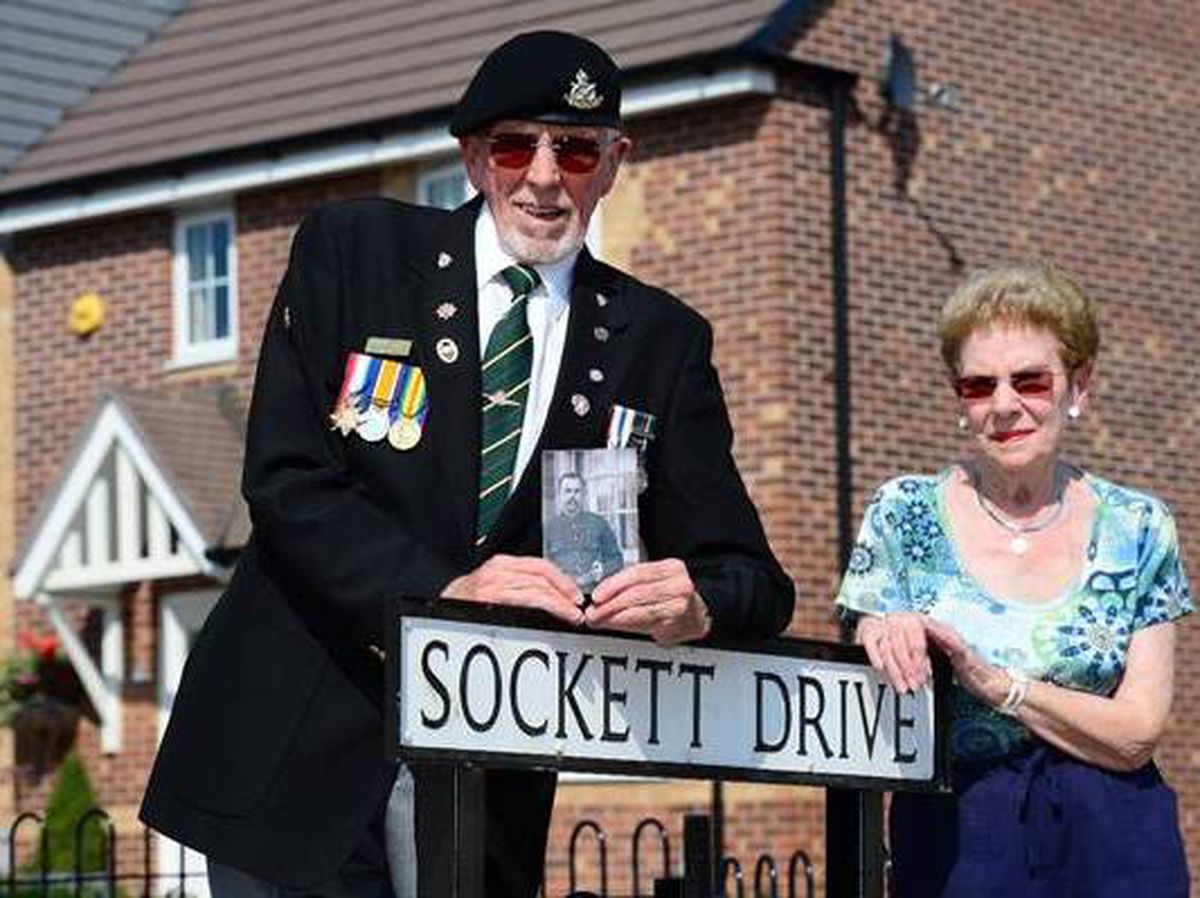 Gordon Taylor holding a picture of his grandfather, William Sockett and his wife, Sylvia