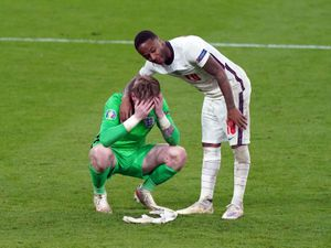 England goalkeeper Jordan Pickford stands dejected with  Raheem Sterling (right)
